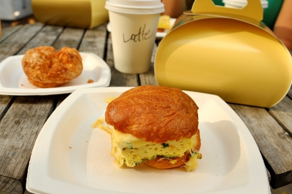 an egg sandwich on a white plate on a table