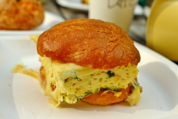 A close up of an egg sandwich on a white plate on a table