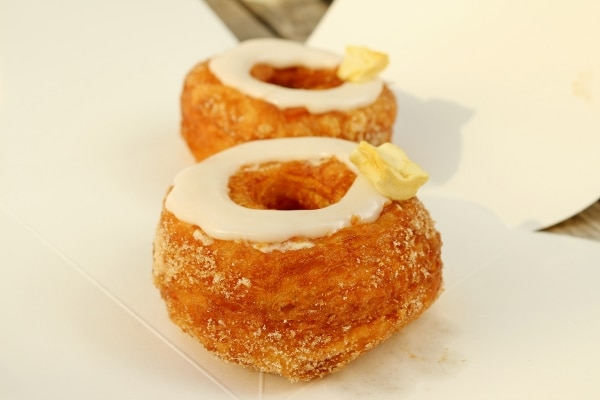 two Cronuts with a ring of white glaze and a piece of dried apple on top