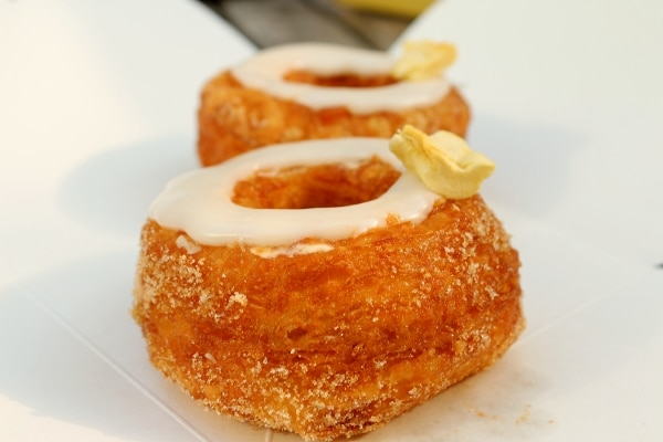 a closeup side view of a Cronut with a ring of white glaze on top