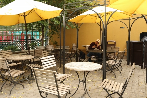 A group of tables and chairs outside with yellow umbrellas