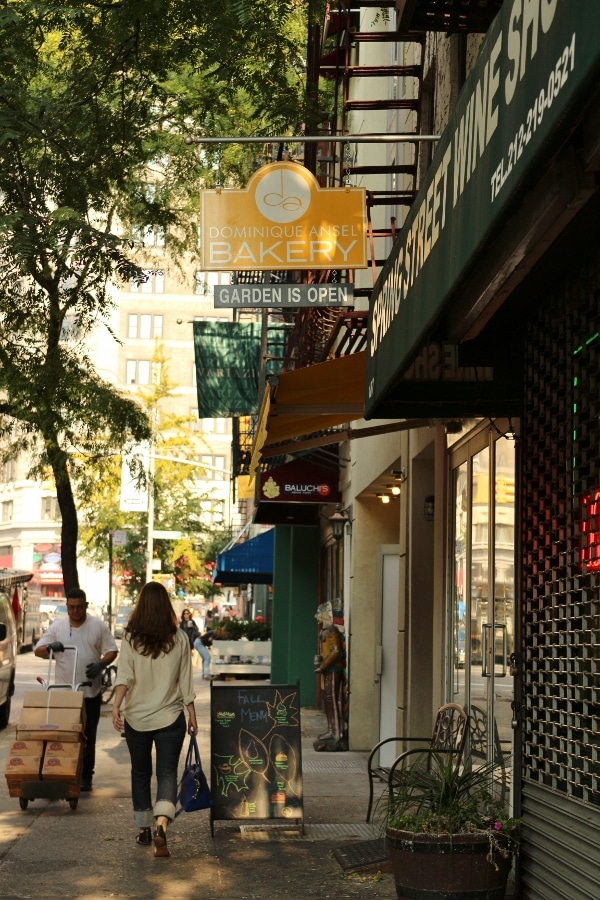 view down a city sidewalk with various shops and people walking