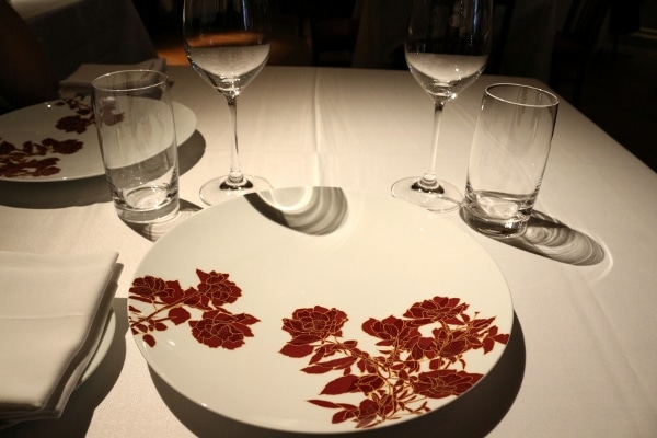a white plate with red flowers on a white tablecloth covered table