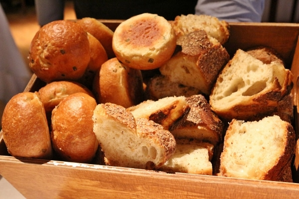 a closeup of a wooden box filled with a variety of bread slices and rolls