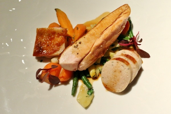 A plate of chicken with round white sausage and colorful vegetables