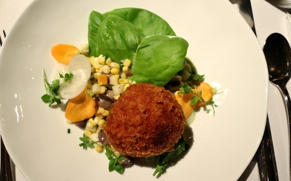 a round fried croquette on a plate with corn and green leaves