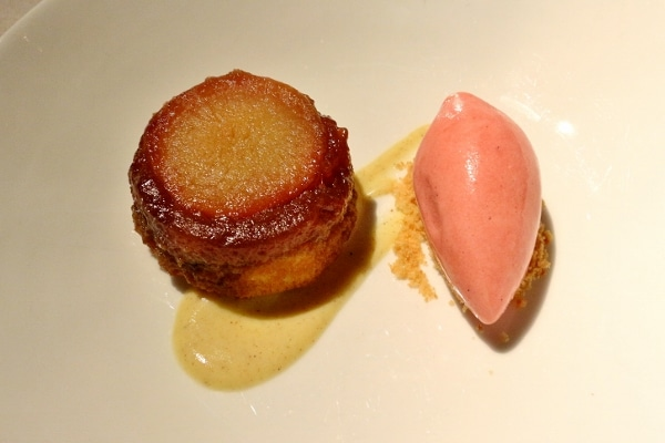 a plate of dessert with a small round pastry and scoop of pink ice cream