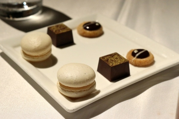 a white square plate with macaron cookies and chocolates on top