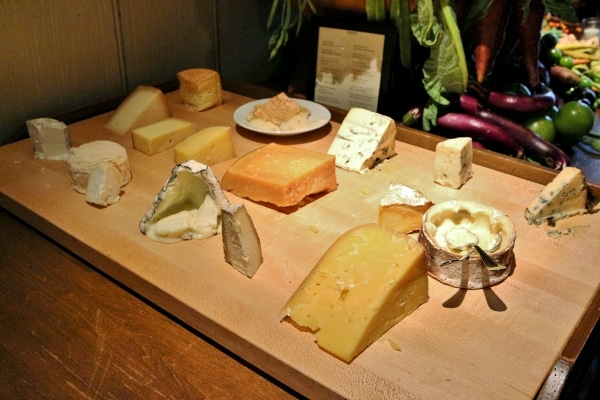 a large wooden board topped with a variety of cheeses