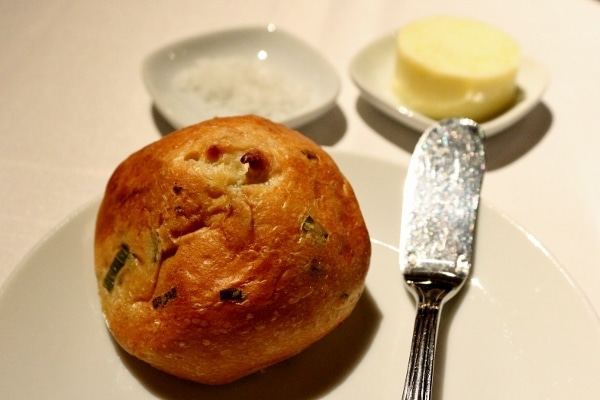 A closeup of a bread roll on a small white plate
