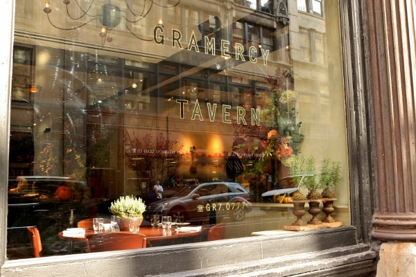 a glass window that says Gramercy Tavern with a view into the restaurant