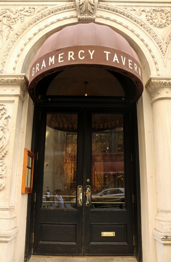 exterior of Gramercy Tavern restaurant with a brown awning over glass double doors