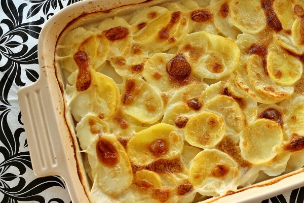overhead view of a rectangular baking dish of sliced potatoes in a bubbly browned cream sauce
