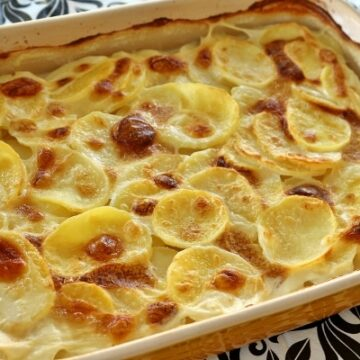 a rectangular baking dish of sliced potatoes in a bubbly browned cream sauce