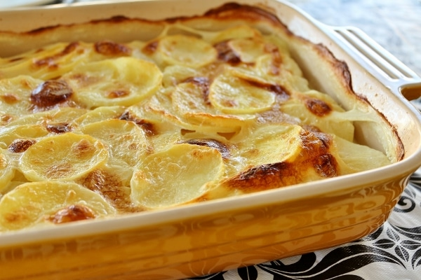 a yellow rectangular baking dish of sliced potatoes in a bubbly browned cream sauce