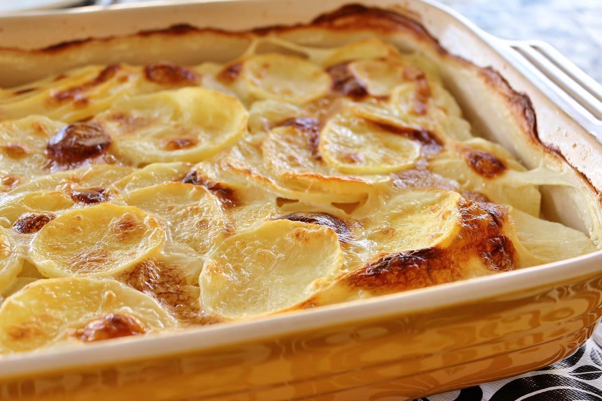Closeup of baked potato gratin in a yellow rectangular casserole dish.