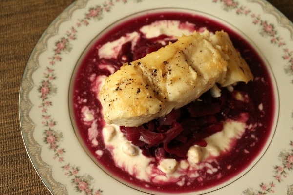 overhead view of a fillet of white fish over cooked red cabbage and a white sauce