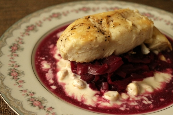 side view of a fillet of white fish over cooked red cabbage and a white sauce