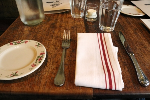 a white and red striped cloth napkin and utensils on a wooden table