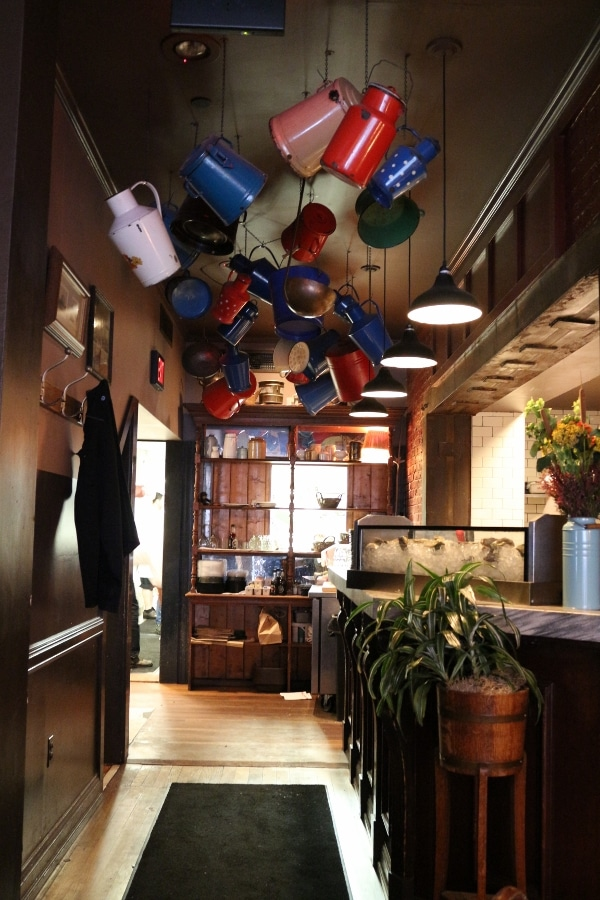 colorful jugs hanging from a wood paneled ceiling