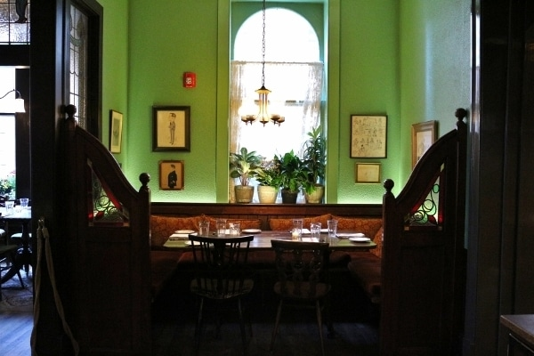 a table with booth seating in front of a bright green wall with a window