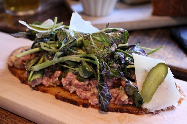 a thin bread toast topped with chopped meat and greens on a wooden board