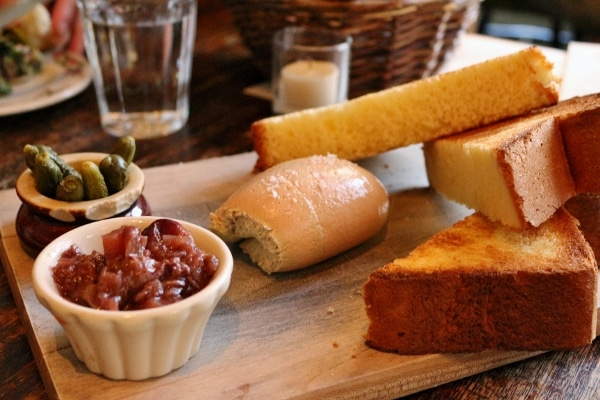 a closeup of a wooden board of pate served with toast and little cups of toppings