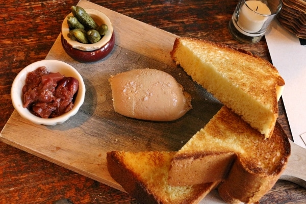 overhead view of a wooden board with toasted bread and pate