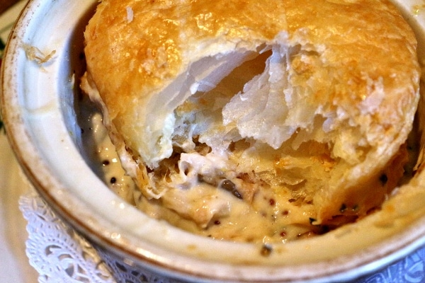a closeup of a half eaten pot pie with a creamy filling and flaky topping