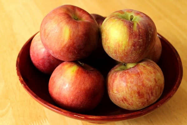 a red bowl full of apples on a wooden table