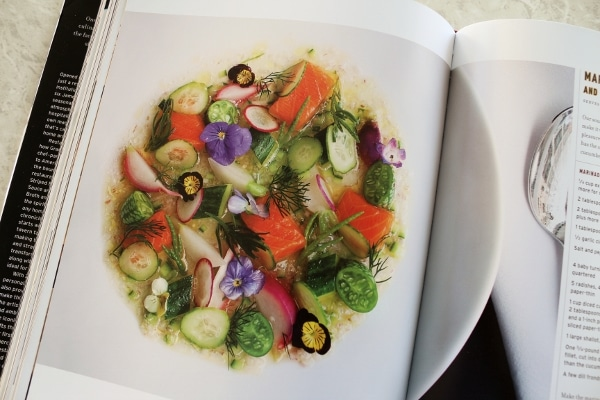a colorful plate of food with pink fish pieces, green vegetables, and purples flowers