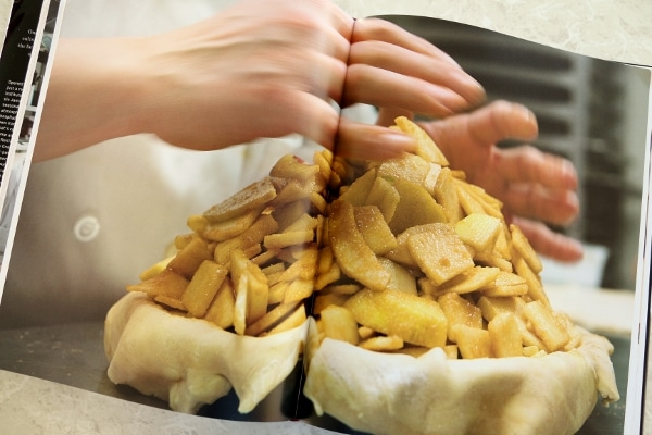 hands piling sliced apples onto a pie crust