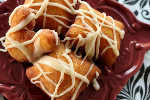 overhead view of a plate of glazed fried beignets in Mickey shapes and squares