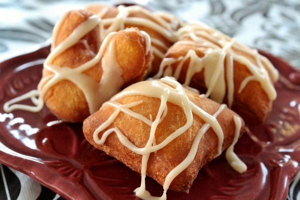 a plate of fried pumpkin beignets drizzled with white glaze