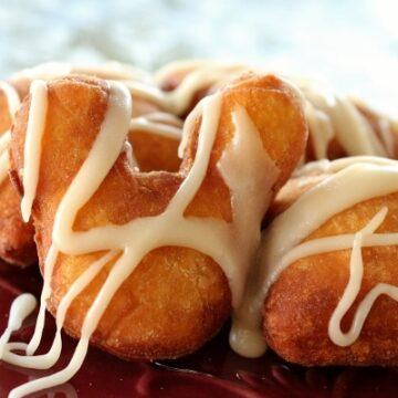 A closeup of a Mickey Mouse shaped fried beignet drizzled with white glaze