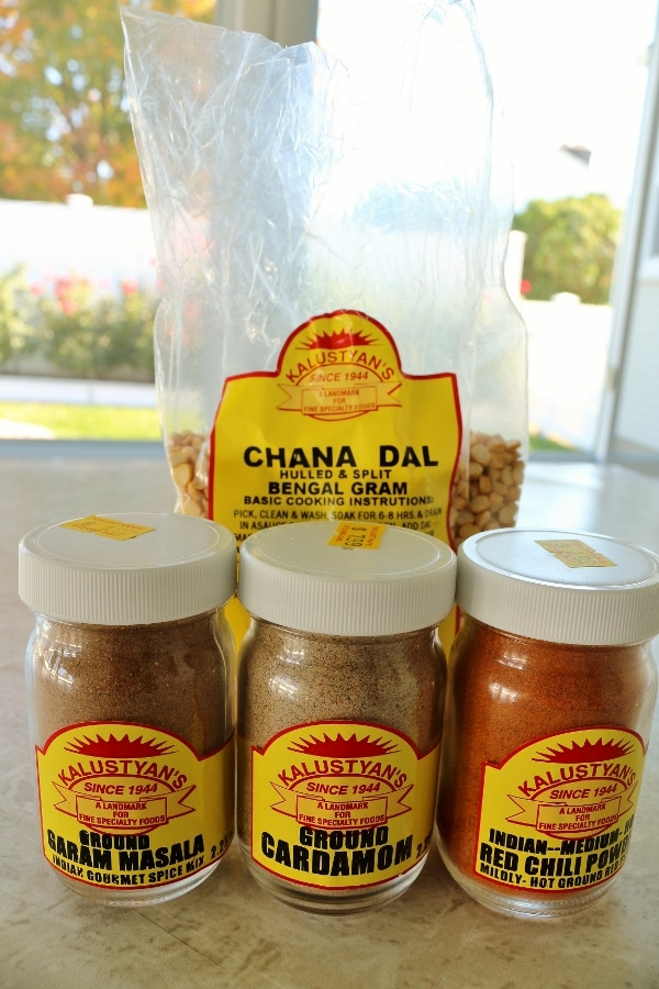 three glass spice containers in front of a bag of chana dal lentils