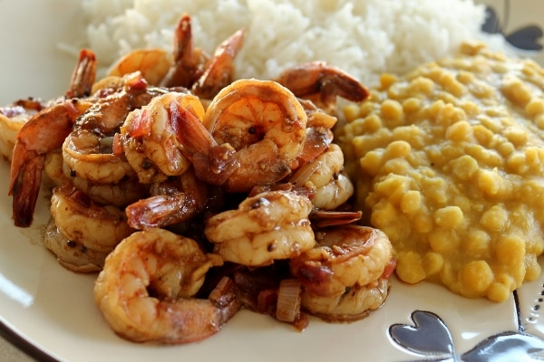 a closeup of shrimp curry on a plate with yellow lentils and white rice