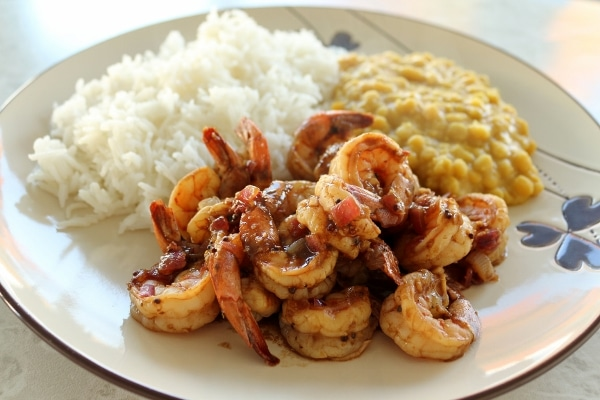 a plate of Indian shrimp curry served with yellow lentils and white basmati rice