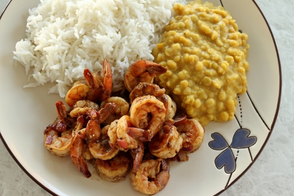 shrimp curry with yellow lentils and white rice on a round plate