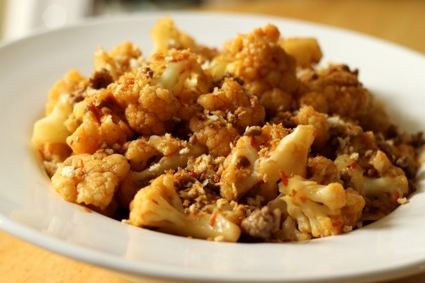 side view of a large bowl of cooked cauliflower sprinkled with panko breadcrumbs