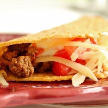 A closeup of a hard taco shell filled with ground beef, tomatoes, and cheese