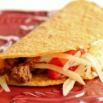 side view of a hard taco with ground beef filling on a dark red plate