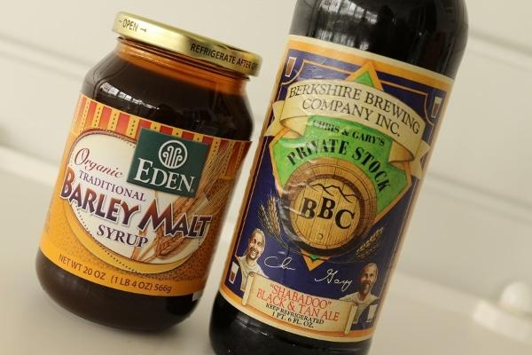 a jar of barley malt syrup next to a bottle of beer