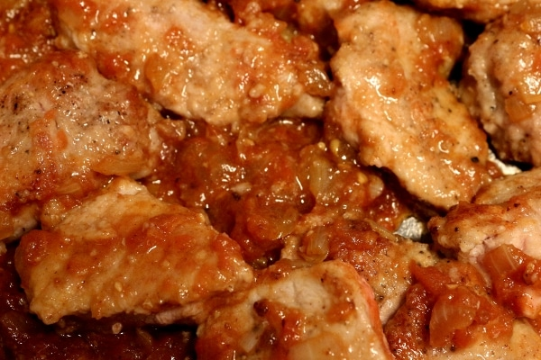 A closeup of pieces of white meat cooking in a reddish sauce