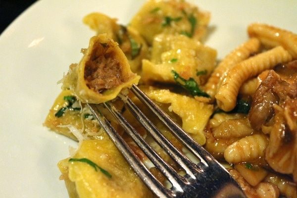 a closeup of a forkful of stuffed pasta bitten to show the meat filling