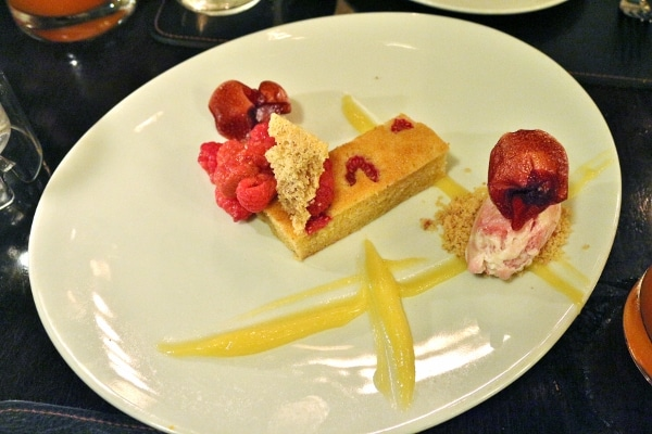 an artfully plated dessert with streaks of citrus curd and raspberries