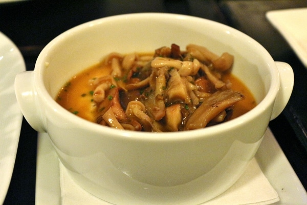 a closeup of a white bowl filled with cooked wild mushrooms