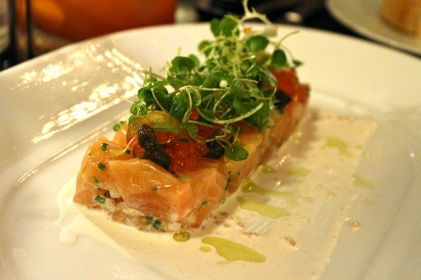 pink fish tartare shaped in a rectangle on a white plate and topped with green herbs