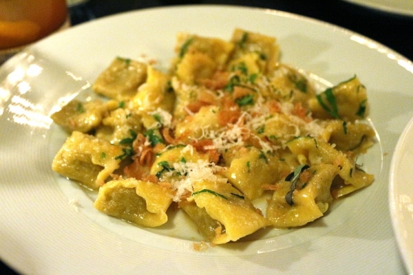 a plate of stuffed pasta with cheese grated over the top