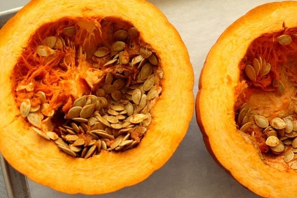 a fresh pumpkin cut in half showing off the seeds inside